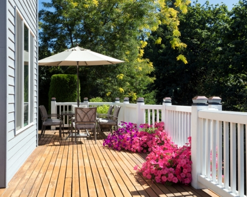 home-cedar-deck-during-bright-summer-day-with-blooming-garden-of-picture-id841029412
